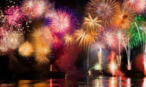 Multicoloured fireworks lighting up the sky and reflecting in the water.