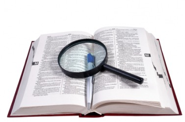 Open dictionary with a magnifying glass and pen on it