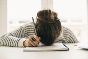 Woman pen in hand head on notebook