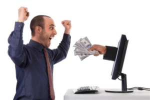 Hand holding money emerging from a computer screen to give the cash to an excited man