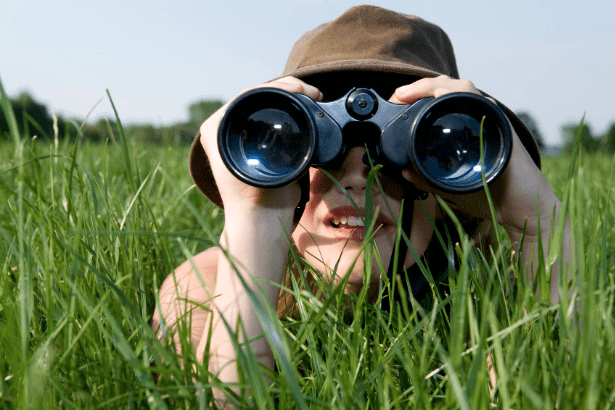 lady laying in deep grass with looking through binoculars