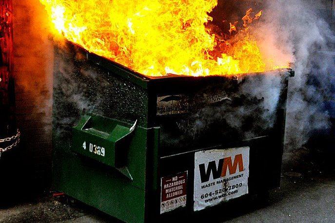 A garbage dumpster bin on fire