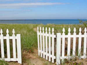 Open white picket gate by the ocean